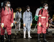 Members of a privately-funded NGO working with county officials wearing protective gather on April 15, 2020, during the dusk-to-dawn curfew imposed by the Kenyan Government, to receive instructions on how to fumigate and disinfect the streets and the stalls at Parklands City Park Market in Nairobi to help curb the spread of the COVID-19 coronavirus. LUIS TATO / AFP