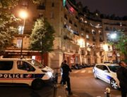 French police stand near their vehicles as they look up to watch people dancing on the balconies of their apartments while music is played by two DJs, Sophie and Clara, during a two-hour party on April 24, 2020 in Paris. Ludovic MARIN / AFP.