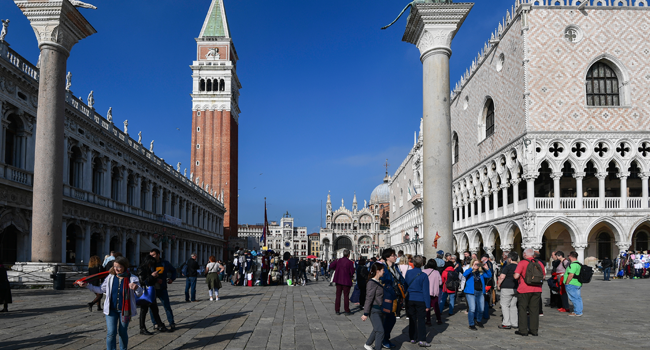 In this file photo taken on November 04, 2019 tourists walk across St Mark's Square (Piazza San Marco) by St. Mark's Campanile (Rear L), St. Mark's Basilica (Basilica San Marco, Rear R) and the Doge's Palace (Palazzo Ducale, R) in Venice. MIGUEL MEDINA / AFP