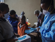 A young boy looks on as a Gauteng Health Department Official adjusts her gloves before collecting samples during a door-to-door COVID-19 coronavirus testing drive in Yeoville, Johannesburg, on April 3, 2020. MARCO LONGARI / AFP