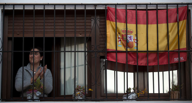 A woman applauds by her window to thank healthcare workers dealing with the COVID-19 coronavirus in Ronda on April 3, 2020 during a national lockdown to prevent the spread of the COVID-19 coronavirus. JORGE GUERRERO / AFP
