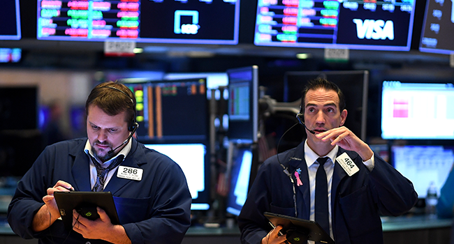 In this file photo Traders work during the opening bell at the New York Stock Exchange (NYSE) on March 19, 2020, at Wall Street in New York City. Johannes EISELE / AFP