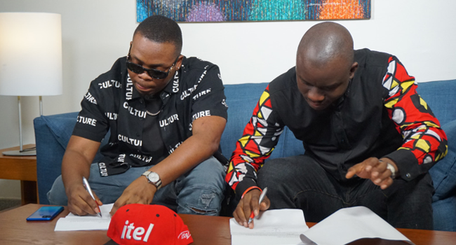 Popstar Olamide (L) signs a branding deal with itel Mobile. The smartphone make announced the deal on May 22, 2020.