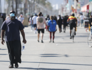 A man wears a face mask along the Venice Beach boardwalk on the day Los Angeles County reopened its beaches, which had been closed due the coronavirus pandemic, on May 13, 2020 in Venice, California.