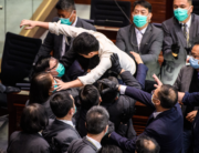 Pro-democracy lawmaker Ted Hui (C) is carried out by security during a scuffle with pro-Beijing lawmakers at the House Committee's election of chairpersons at the Legislative Council in Hong Kong on May 18, 2020. Anthony WALLACE / AFP