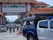 Chinese border police guards keep watch as migrant workers return from China at the Myanmar border gate in Muse in Shan state on May 12, 2020. Phyo Maung Maung / AFP