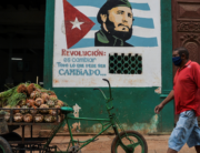"A man wearing a face mask walks near a sign depicting Cuban late leader Fidel Castro and reading ""Revolution is to change everything that needs to be changed"", in Havana on May 13, 2020, amid the new coronavirus pandemic. YAMIL LAGE / AFP"