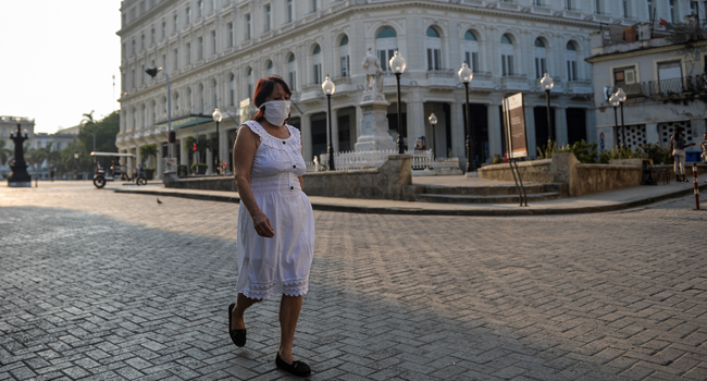 A woman wearing a face mask walks in a street of Havana, Cuba, on May 19, 2020, amid the new coronavirus pandemic. YAMIL LAGE / AFP