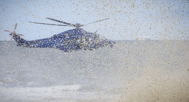 The downdraft from a police helicopter blows away surf from beachside rocks in Scheveningen, The Netherlands, on May 14, 2020. Sem VAN DER WAL / ANP / AFP