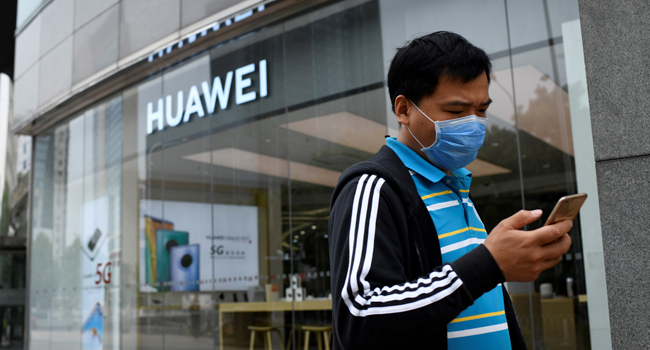 A man wearing a face mask uses his mobile phone as he walks past a Huawei store in Beijing on May 16, 2020. WANG Zhao / AFP