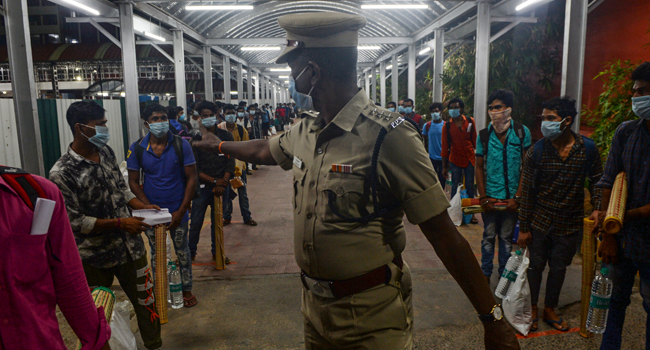 A security personnel (C) directs stranded migrant labourers queueing to board a special train to Odisha from MGR Central railway station after the government eased a nationwide lockdown imposed as a preventive measure against the COVID-19 coronavirus, in Chennai on May 9, 2020. Arun SANKAR / AFP