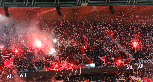 In this file photo taken on February 09, 2020 Fans light flares in the stands during the French L1 football match between Paris Saint-Germain (PSG) and Lyon (OL) at the Parc des Princes stadium in Paris. GEOFFROY VAN DER HASSELT / AFP