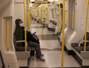 Commuters wearing PPE (personal protective equipment) including face masks as a precautionary measure against COVID-19, travel by public transport during the evening 'rush hour', on TfL (Transport for London) Circle Line underground trains, in central London on May 14, 2020. ISABEL INFANTES / AFP