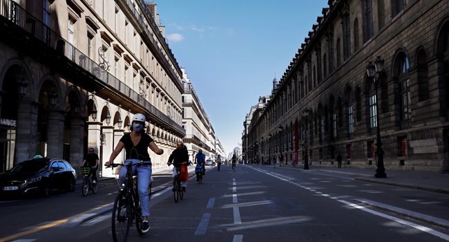 People cycle with their bike down the Rue de Rivoli, by the Louvre museum, in Paris on May 19, 2020 as France eases lockdown measures taken to curb the spread of the COVID-19 (the novel coronavirus). THOMAS COEX / AFP