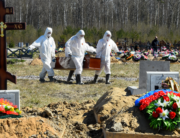 Cemetery workers wearing protective gear bury a coronavirus victim at a cemetery on the outskirts of Saint Petersburg on May 6, 2020. OLGA MALTSEVA / AFP
