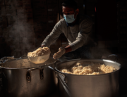 A kitchen worker prepares hot meals at Thava Indian restaurant, at The Gardens, for the daily food distribution in an informal settlement in Tembisa, Johannesburg, on April 24, 2020. Luca Sola / AFP