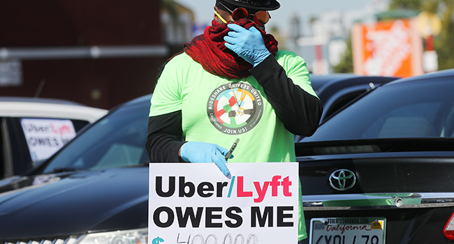 In this file photo taken on April 16, 2020, a protestor displays a sign as Uber and Lyft drivers with Rideshare Drivers United and the Transport Workers Union of America prepare to conduct a caravan protest outside the California Labor Commissioners office amidst the coronavirus pandemic in Los Angeles, California.  MARIO TAMA / GETTY IMAGES NORTH AMERICA / AFP