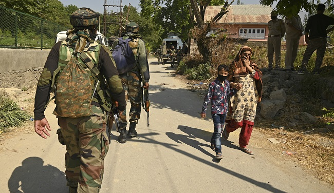 A woman with her child walks past Indian army soldiers near a mosque at the site of a gunbattle at Meej Pampore area of Pulwama district, south of Srinagar on June 19, 2020. - Indian forces have killed eight militants in restive Kashmir, including two who hid in a mosque, officials said on June 19, as New Delhi escalates counter-insurgency efforts in the disputed territory. (Photo by Tauseef MUSTAFA / AFP)