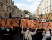 Demonstrators hold placards during a protest arranged by the 'Rhodes Must Fall' campaign, calling for the removal of a statue of British businessman and imperialist Cecil John Rhodes, from outside Oriel College at the University of Oxford in Oxford, west of London on June 9, 2020. Adrian DENNIS / AFP