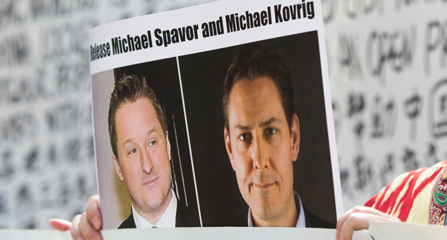 In this file photo taken on May 8, 2019, Turnisa Matsedik-Qira, of the Vancouver Uyghur Association, demonstrates against China's treatment of Uighurs while holding a photo of detained Canadians Michael Spavor (L) and Michael Kovrig outside a court appearance for Huawei Chief Financial Officer, Meng Wanzhou at the British Columbia Supreme Court in Vancouver. Jason Redmond / AFP