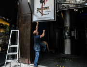 Employees remove movie posters outside The Max Linder Cinema Theatre in Paris on June 18, 2020, ahead of the re-opening of cinema halls and theatres, as France eases lockdown measures taken to curb the spread of the Covid-19 pandemic (novel coronavirus). STEPHANE DE SAKUTIN / AFP
