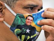 A supporter of President Jair Bolsonaro wears a face mask with Bolsonaro's image during a demonstration at Copacabana beach in Rio de Janeiro, Brazil, on June 7, 2020. CARL DE SOUZA / AFP