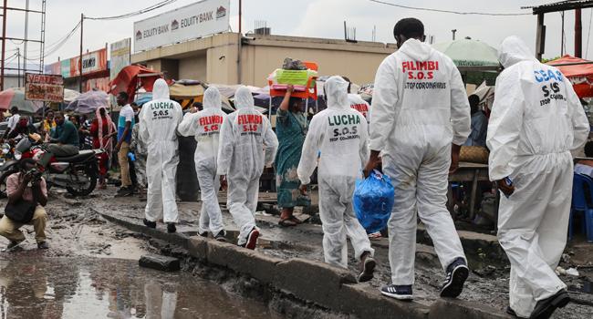 Activists walk along the street during a COVID-19 coronavirus awareness campaign in Kinshasa on May 29, 2020. SAMIR TOUNSI / AFP