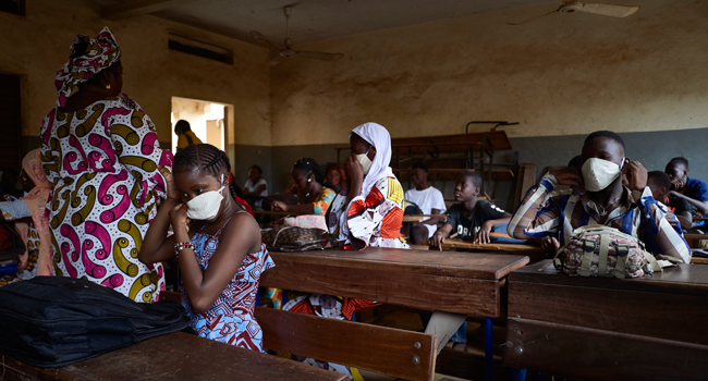 Malian pupils wear face masks in the classroom of a school as the government decided to resume lessons after two months of closure due to the spread of COVID-19 coronavirus, in Bamako on June 2, 2020. MICHELE CATTANI / AFP