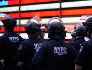 "In this file photo taken on June 01, 2020 NYPD police officers watch demonstrators in Times Square during a ""Black Lives Matter"" protest. TIMOTHY A. CLARY / AFP"