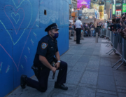 A New York City police officer takes a knee during a demonstration by protesters in Times Square over the death of George Floyd by a Minneapolis police officer at a rally on May 31, 2020 in New York. Bryan R. Smith / AFP