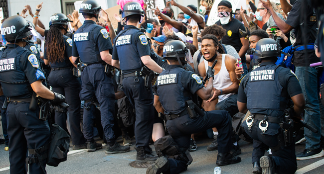 A man screams with emotion as he sees a policeman take a knee while hundreds protest the death of George Floyd next to the White House on May 31, 2020 in Washington, DC. ROBERTO SCHMIDT / AFP
