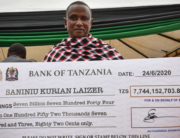 Tanzanian small-scale miner Saniniu Kuryan Laizer, 52, poses with the enlarged cheque copy from the government after selling two of the biggest of the country's precious gemstones, Tanzanite, during the ceremony for his historical discovery in Manyara, northern Tanzania, on June 24, 2020. Filbert RWEYEMAMU / AFP