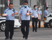 Police officers carry food as they walk in the grounds of a closed bus station near the closed Xinfadi market in Beijing on June 13, 2020. GREG BAKER / AFP