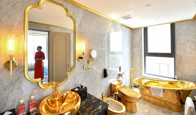A staff member poses for a photograph inside the 1,000 USD per night executive two bedroom suite of the newly-inaugurated Dolce Hanoi Golden Lake hotel, the world's first gold-plated hotel, in Hanoi on July 2, 2020. (Photo by Manan VATSYAYANA / AFP)