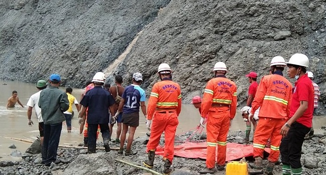 This handout from the Myanmar Fire Services Department taken and released on July 2, 2020 shows rescuers attempting to locate survivors after a landslide at a jade mine in Hpakant, Kachin state. - The bodies of at least 50 jade miners were pulled from the mud on July 2 after a landslide in northern Myanmar, fire services said, as monsoon rains worsen already deadly conditions. (Photo by Handout / MYANMAR FIRE SERVICES DEPARTMENT / AFP) /