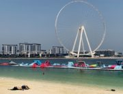 A man sunbathes along the Marina beach near the Ain Dubai Ferris wheel in the Gulf emirate of Dubai on July 7, 2020. (Photo by Giuseppe CACACE / AFP)
