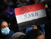 A protester holds a Yemeni flag-themed placard in Parliament Square in London on July 5, 2020, as she demonstrates against the continued conflict in Yemen. - Yemen has been locked in conflict since the Huthis took control of Sanaa in 2014 and went on to seize much of the north. The crisis escalated when the Saudi-led coalition intervened the following year to support Yemen's internationally-recognised government. Tens of thousands of people, mostly civilians, have been killed and millions displaced in what the United Nations has called the world's worst humanitarian disaster. (Photo by JUSTIN TALLIS / AFP)