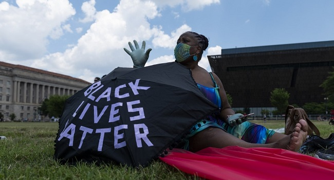 A woman sits near her umbrella during a small rally against racism in the US next to the Washington Memorial in Washington, DC, on July 4, 2020, ahead of the Independence Day celebrations. - Wide spread national protests over police brutality and systemic racism have taken place following the police killing of George Floyd in Minneapolis in May. (Photo by ROBERTO SCHMIDT / AFP)