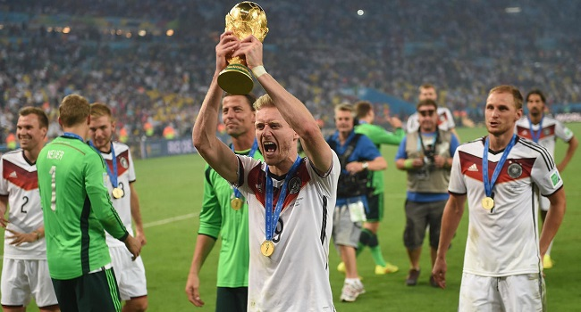 Germany forward Andre Schuerrle holds up the World Cup trophy in Rio de Janeiro after Germany won the final of Brazil 2014. (AFP Photo/PATRIK STOLLARZ)