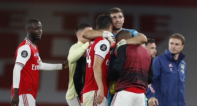 Arsenal's Argentinian goalkeeper Emiliano Martinez (C) celebrates with teammates on the pitch after the English Premier League football match between Arsenal and Liverpool at the Emirates Stadium in London on July 15, 2020. - Arsenal won the game 2-1. (Photo by PAUL CHILDS / POOL / AFP) / RESTRICTED TO EDITORIAL USE. No use with unauthorized audio, video, data, fixture lists, club/league logos or 'live' services. Online in-match use limited to 120 images. An additional 40 images may be used in extra time. No video emulation. Social media in-match use limited to 120 images. An additional 40 images may be used in extra time. No use in betting publications, games or single club/league/player publications. /