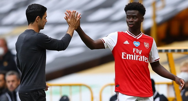 Arsenal's Spanish head coach Mikel Arteta (L) high-fives Arsenal's English striker Bukayo Saka (R) as Saka goes off substituted during the English Premier League football match between Wolverhampton Wanderers and Arsenal at the Molineux stadium in Wolverhampton, central England on July 4, 2020. (Photo by Michael Steele / POOL / AFP)