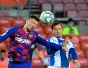 Barcelona's French defender Clement Lenglet (L) vies with Espanyol's Spanish forward Javier Puado during the Spanish League football match between Barcelona and Espanyol at the Camp Nou stadium in Barcelona on July 8, 2020. (Photo by LLUIS GENE / AFP)