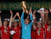 Bayern Munich's German goalkeeper Manuel Neuer raises the German Cup (DFB Pokal) trophy as he and his teammates celebrate winning the final football match Bayer 04 Leverkusen v FC Bayern Munich at the Olympic Stadium in Berlin on July 4, 2020. (Photo by Alexander Hassenstein / POOL / AFP)