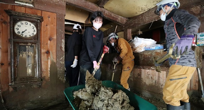 High school students shovel off the mud from a ryokan, a traditional Japanese style hotel, in the aftermath of heavy flooding in Hitoyoshi, Kumamoto prefecture on July 9, 2020. - Japanese emergency services and troops scrambled on July 9 to reach thousands of homes cut off by catastrophic flooding and landslides that have killed dozens and caused widespread damage. (Photo by STR / JIJI PRESS / AFP) / Japan OUT