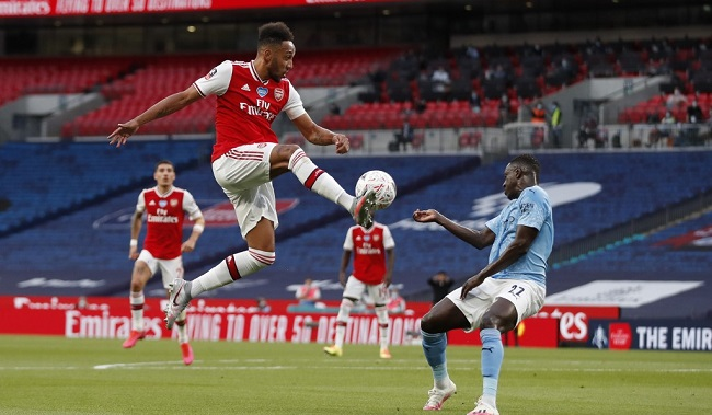 Arsenal's Gabonese striker Pierre-Emerick Aubameyang (L) leaps for the ball as Manchester City's French defender Benjamin Mendy (R) defends during the English FA Cup semi-final football match between Arsenal and Manchester City at Wembley Stadium in London, on July 18, 2020. (Photo by MATTHEW CHILDS / POOL / AFP) / NOT FOR MARKETING OR ADVERTISING USE / RESTRICTED TO EDITORIAL USE