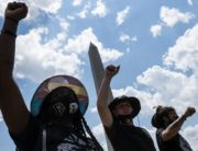 Protesters raise their fists during a small rally against racism in the US next to the Washington Memorial in Washington, DC, on July 4, 2020, ahead of the Independence Day celebrations. - Wide spread national protests over police brutality and systemic racism have taken place following the police killing of George Floyd in Minneapolis in May. (Photo by ROBERTO SCHMIDT / AFP)