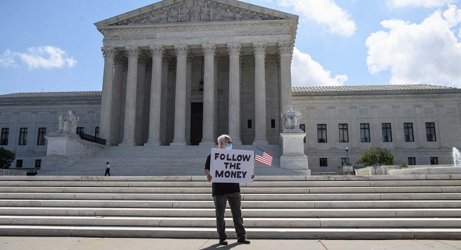 A man holds a sign in front of the US Supreme Court in Washington, DC, on July 9, 2020. - The court ruled that US President Donald Trump must hand over financial records to prosecutors in New York. In a 7-2 ruling, the court said the president does not have absolute immunity from criminal investigation. (Photo by NICHOLAS KAMM / AFP)