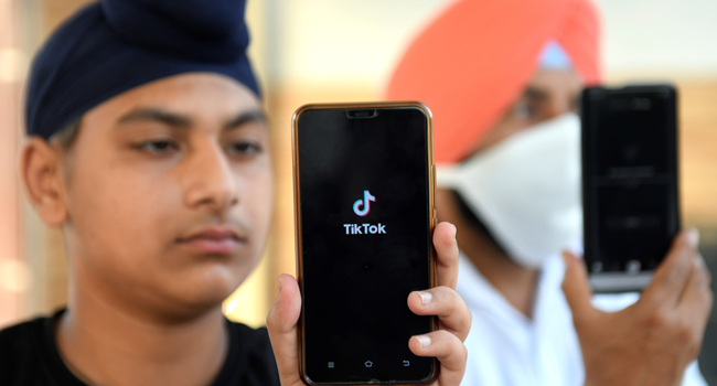 In this file photo taken on June 30, 2020, Indian mobile users browse through the Chinese owned video-sharing 'Tik Tok' app on smartphones in Amritsar. NARINDER NANU / AFP