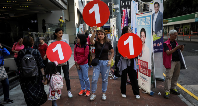 This file photo taken on November 24, 2019 shows political campaigners holding up signs to arriving voters during the district council elections in North Point in Hong Kong.  VIVEK PRAKASH / AFP