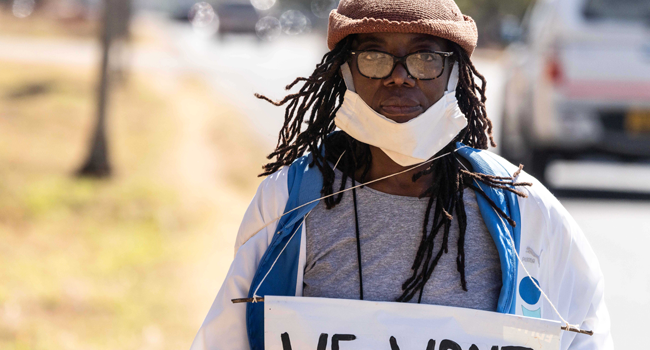 Zimbabwean novelist Tsitsi Dangarembga holds a placard during an anti-corruption protest march along Borrowdale road, on July 31, 2020 in Harare. ZINYANGE AUNTONY / AFP